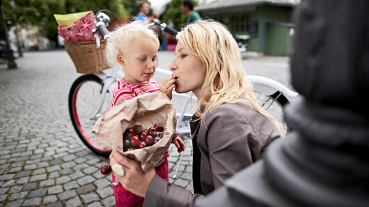 Photo of a mother eating cherries