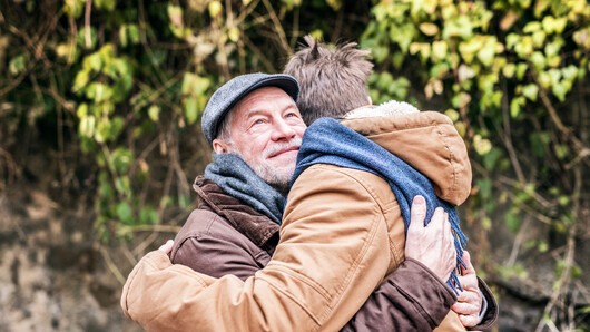 Senior citizen and young volunteer hugging. Illustration photo.