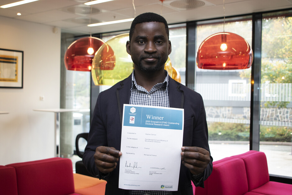 Picture of Stephen Zamore holding his winning certificate.