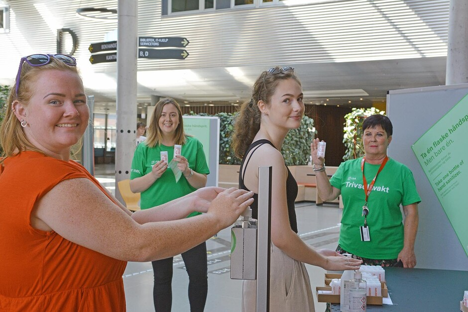 "LAST AUTUMN: Gunn Kristine (to the left) and Marie were in a hurry but stopped anyway to use hand sanitiser at the main entrance at Campus Kristiansand. Behind them are the ""trivselsvakter"" Amna Drace (to the left) and Elin Gauslaa ready to give out refillable pocket-sized hand sanitiser bottles. (Stock photo)"