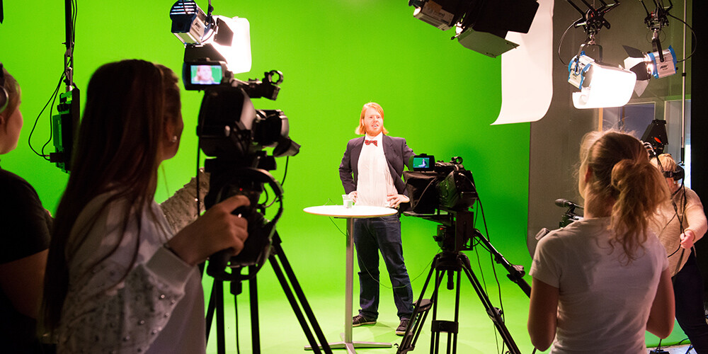 Studenter filmer foran green screen.